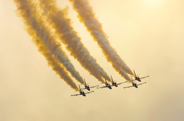 Group of fighter airplanes fly up with a smoke track against a orange sky with clouds.