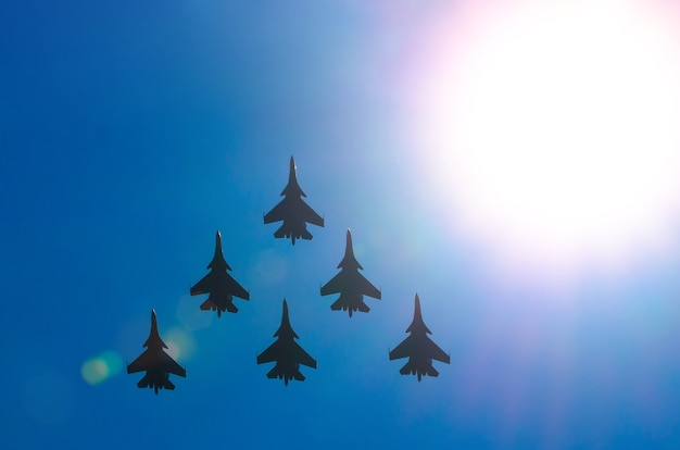 Group of fighter jet airplane sun glow blue sky.
