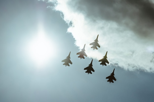 Group of fighters in the sky in the violet sunshine lighted up.