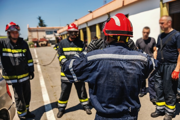 Group of firemen standing outdoors in protective uniforms and helmets and preparing for action.
