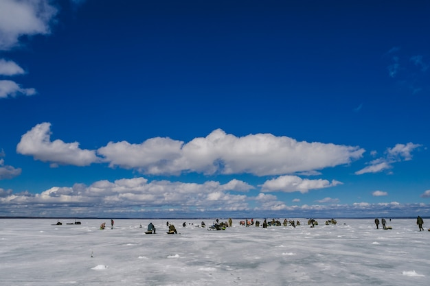 Group of fishermen fishing on the ice pond