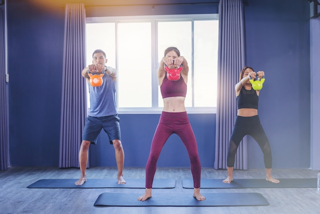 Group of fit peoples holding kettle bell during an exercise class at the fitness gym.