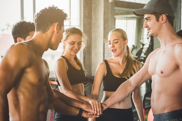 Group of fitness people men and woman put the hands together for team work. happy fitness workout team concept.
