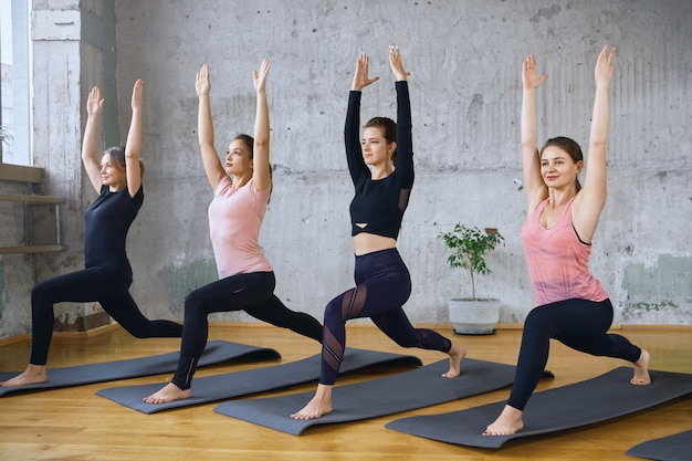 Group of fitnesswomen stretching on mats.