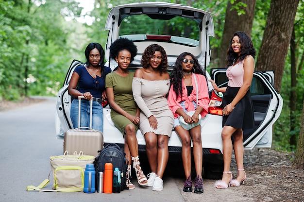 Group of five happy traveler women sitting in car open trunk
