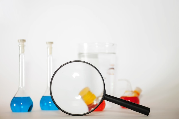 Group of flasks and test tubes in chemical laboratory. reagents and samples of acid suspensions behind magnifying glass on laboratory table. conical flasks of different colors on white background