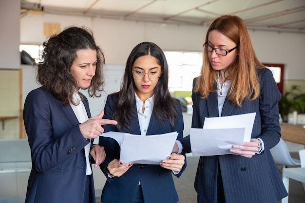 Group of focused young women studying new project