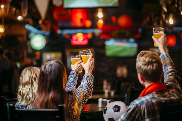 Group of football fans with scarf and ball watching match and drinks beer in sports bar. tv broadcasting, young friends leisures in pub, favorite team wins