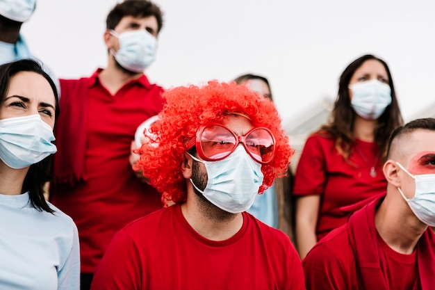 Group of football team supporters in face mask watching concentrated the match