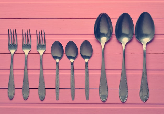 A group of forks, a spoons on a pink wooden table