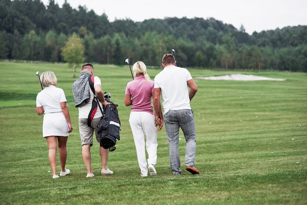 Group of four friends carying golf equipment going to the next point of the field.