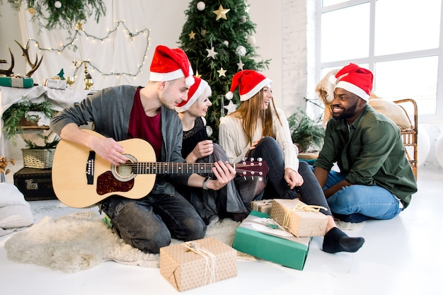 Group of four friends celebrating christmas at home playing guitar and singing carols