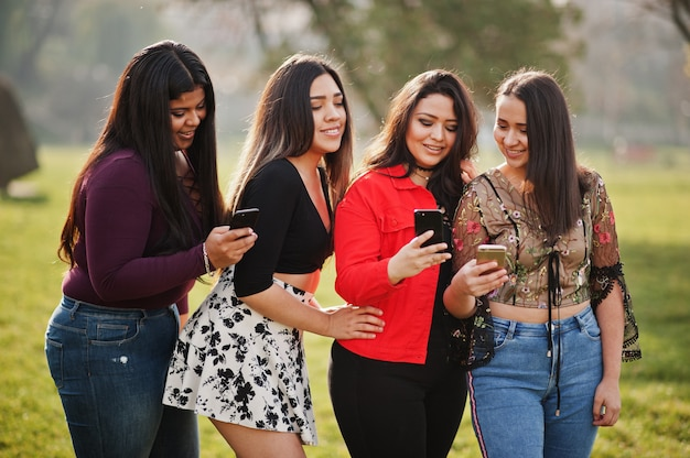 Group of four happy and pretty latino girls from ecuador posed at street and looking at mobile phones.