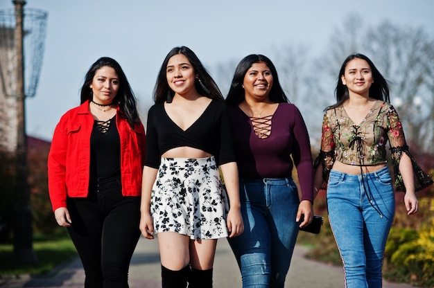 Group of four happy and pretty latino girls from ecuador posed at street.