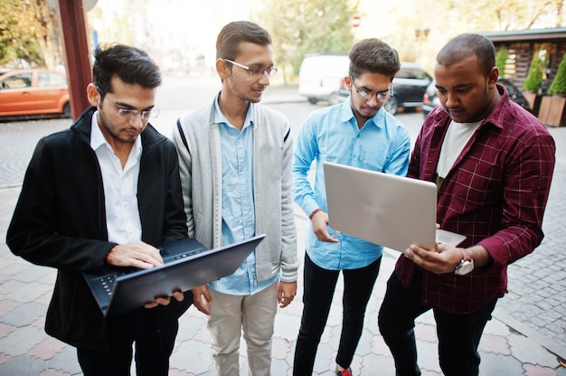Group of four indian teen male students. classmates spend time together and work at laptops.
