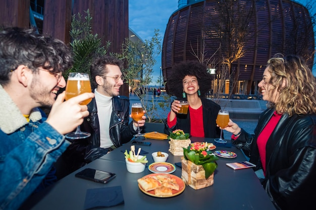 Group of four multiethnic friends sitting outdoor club drinking beer making toast