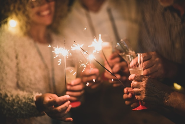 Group of four people having fun and enjoying holding glasses of champagne and sparklers celebrating the happy new year together