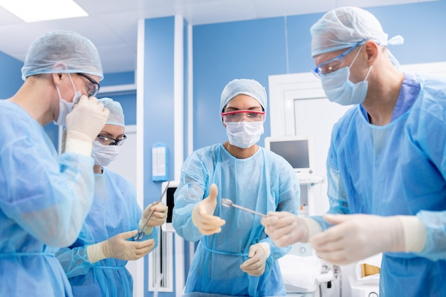 Group of four professionals in protective uniform, gloves and masks taking surgical instruments before making operation in surgery room