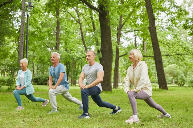 Group of four senior men and women wearing sports clothes doing leg stretching exercise in park