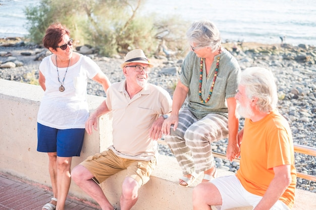 Group of four seniors and mature people together at the beach sitted on a bench or wall and talking - two couples in vacations together at the sea - ocean and water at the background