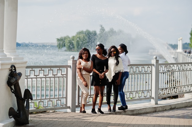 Group of four women having fun against lake with fountains