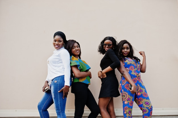 Group of four women posed outdoor against wall