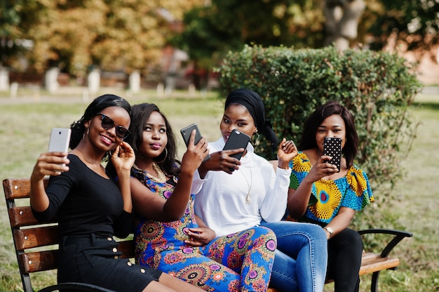 Group of four women sitting on bench outdoor with mobile phones at hands and making selfie