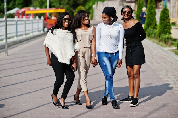 Group of four women walking at city on sunny day