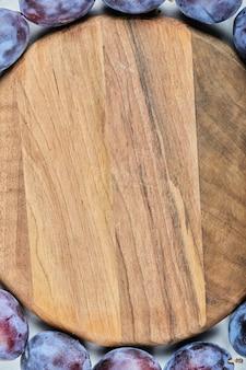 Gruppo di prugne fresche intorno al piatto di legno. foto di alta qualità