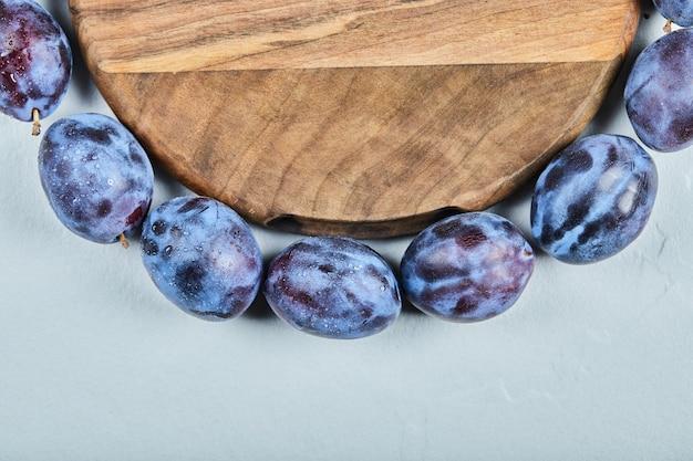 Gruppo di prugne fresche intorno al piatto di legno.