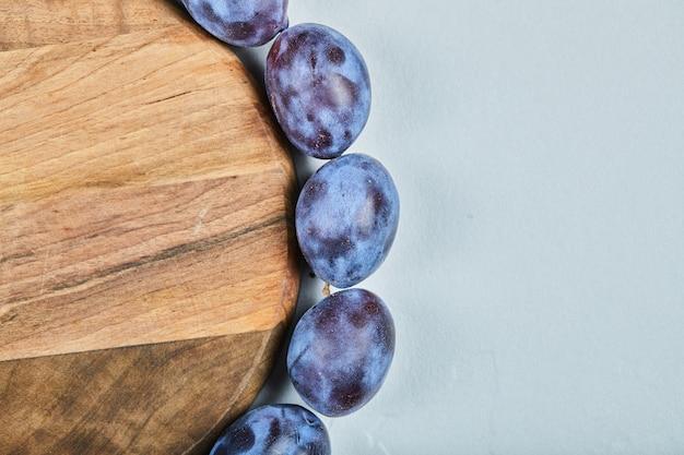 Gruppo di prugne fresche intorno al piatto di legno