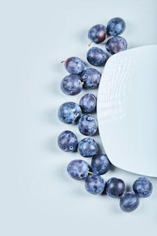 Gruppo di prugne fresche su sfondo blu. foto di alta qualità