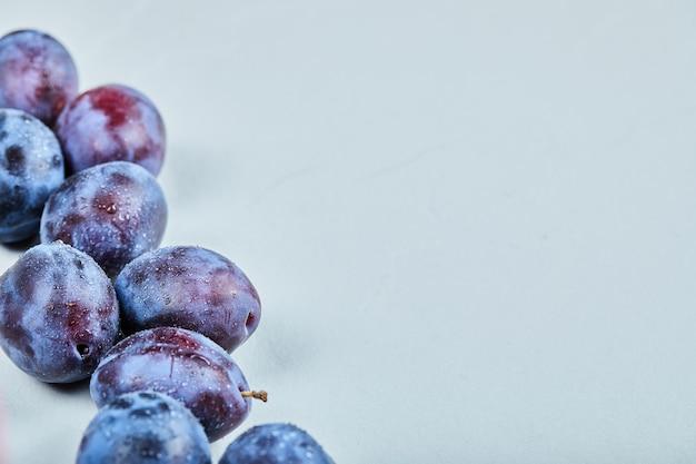 Gruppo di prugne fresche su sfondo blu