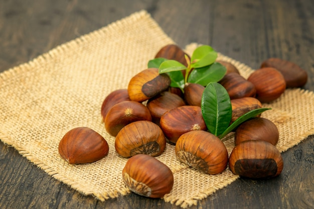 Group of fresh ripe chestnuts on the rustic sackcloth and on the natural wooden background.