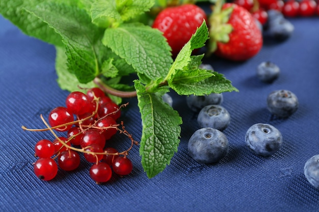 Group of fresh summer berries with mint on blue tablecloth