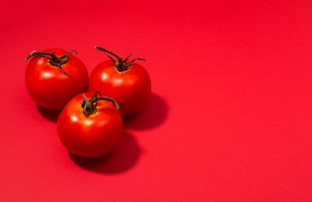 Group of fresh tomatoes presented on red table