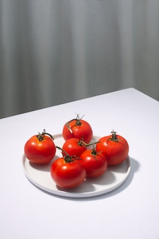 Group of fresh tomatoes presented on white table