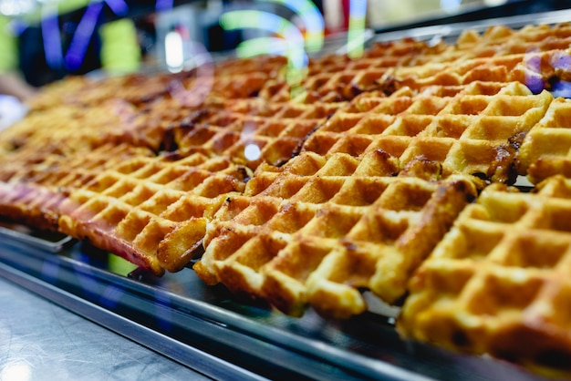 Group of freshly baked waffles ready to be savored for sale at a fair.