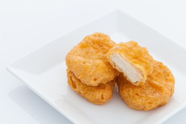 Group of fried chicken nuggets i on white dish
