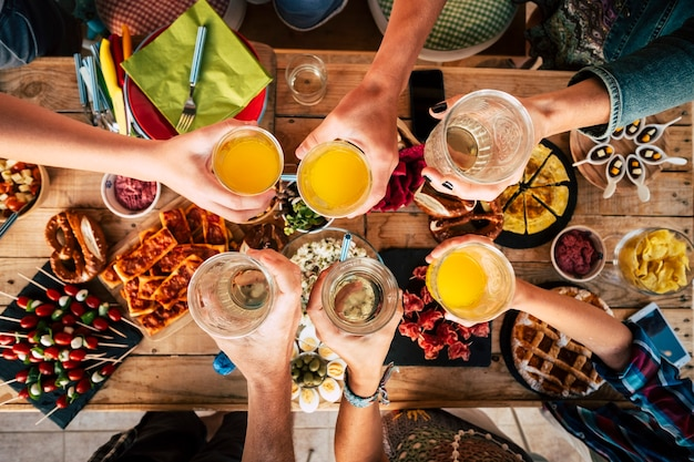 Group of friend mixed ages  generations from children to adult have fun togeter with food and drinks - aerial top view of table and people toasting together in friendship - home or restaurant concept