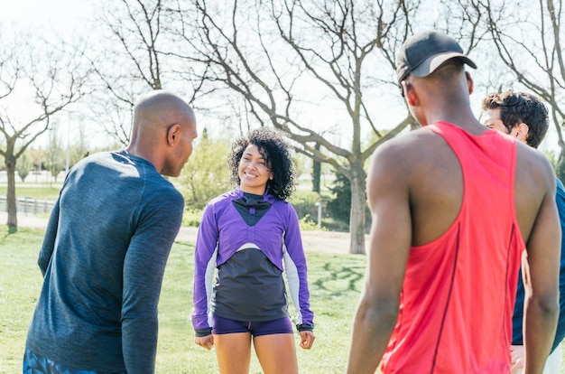 Group of friendly runners talking in a park before training. selective focus.