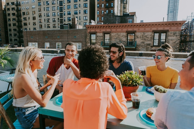 Group of friends apending time together on a rooftop in new york city, lifestyle concept with happy people