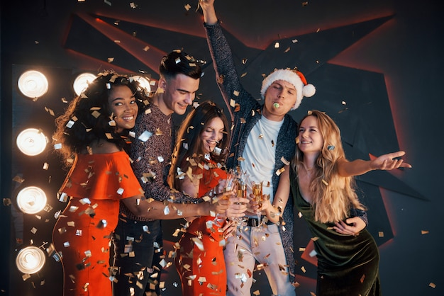 A group of friends are having fun in beautiful chiffon dresses with champagne and confetti, preparing for the new year