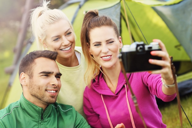 Group of friends camping in forest and taking selfie