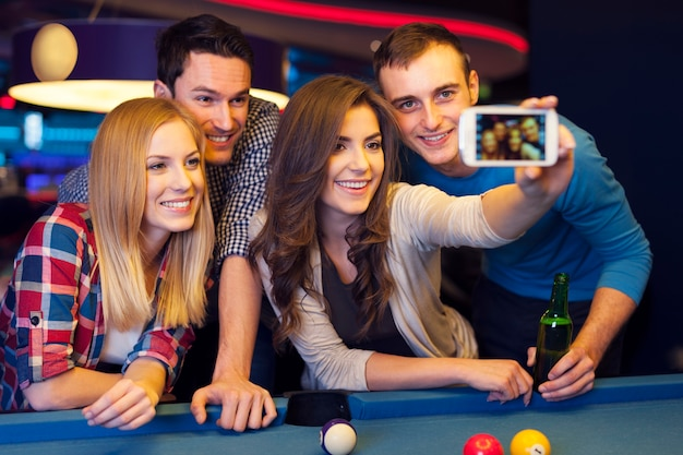 Group of friends catching memories from billiard club