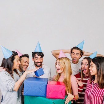 Group of friends celebrating birthday with boxes