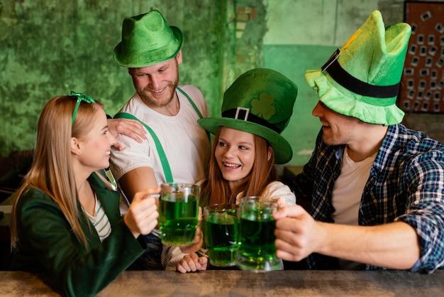 Gruppo di amici che celebrano st. patrick's day insieme ai drink al bar