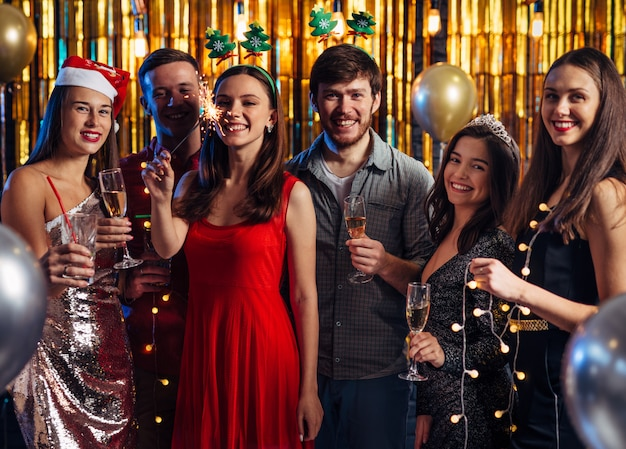 Group of friends celebrating with fireworks and glasses enjoying christmas party