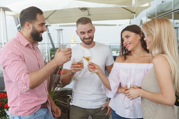 Group of friends chatting joyfully, having drinks at rooftop bar