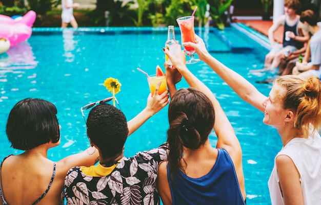 Group of friends cheers drinks at the pool